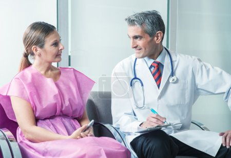 Photo pour Male doctor speaking to female patient in a reassuring way. - image libre de droit