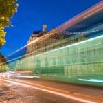 Car light trails across Paris avenues at night....