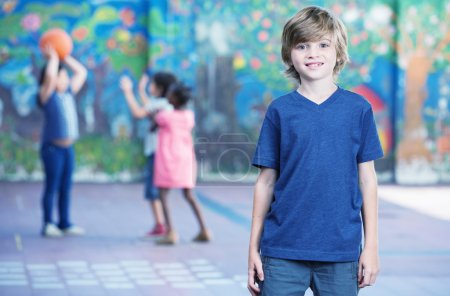 Photo for Happy kid smiling in schoolyard with other chilldren playing on background. - Royalty Free Image
