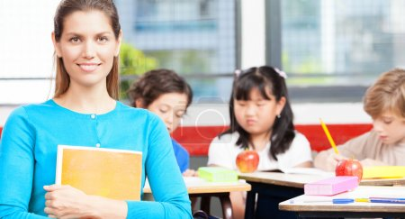 Happy female teacher in a multi ethnic elementary classroom