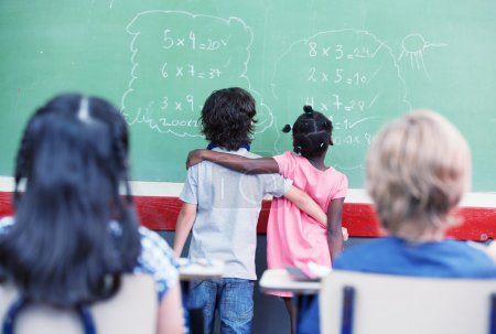 elementary school students at chalkboard