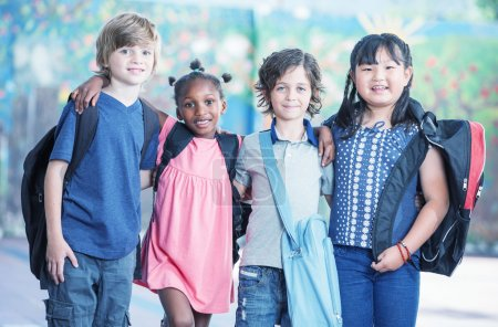 Happy multi race classroom embracing in the schoolyard