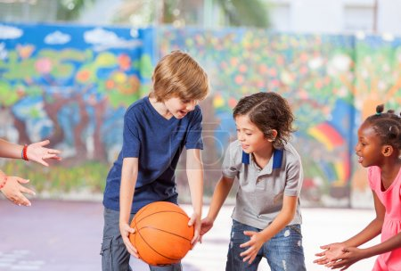 Photo for Elementary school children happy playing basketball at school. - Royalty Free Image