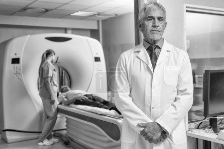Confident male doctor in hospital with patient undergoing mri