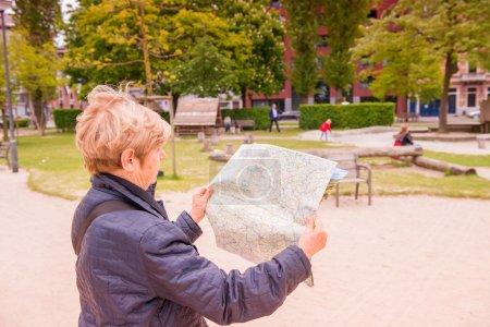 Senior woman looking at map while visiting city