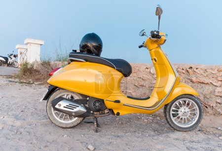 Yellow scooter against blue sky