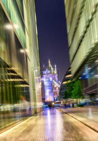 Blurred view of illuminated Tower Bridge framed by buildings ref