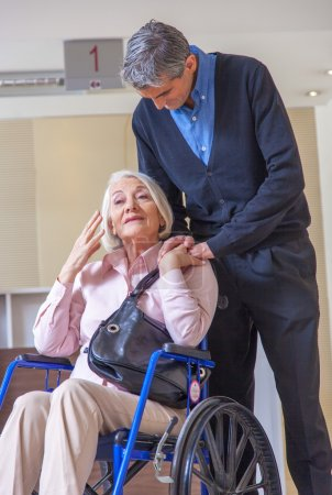 Woman on wheelchair with  assistant