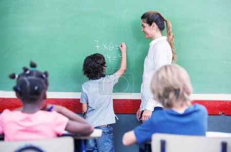 Photo for Kid writing math at chalkboard during a lesson with teacher and other children in the classroom - Royalty Free Image