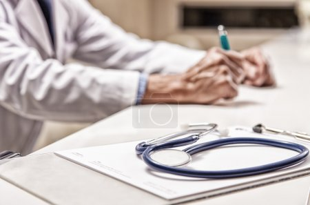 Stethoscope with doctor in background
