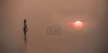 Mobile phone antenna tower emerges from the fog over a sunset sk