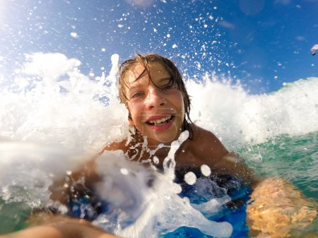 boy enjoys riding the waves with a surfboard