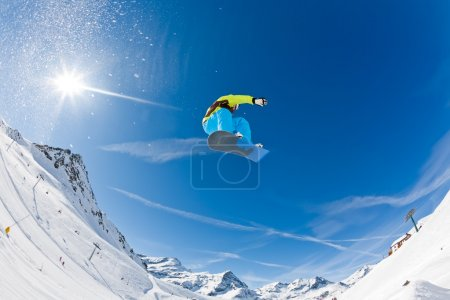 Photo for Snowboarder launching off a jump; Gressoney , Aosta, Italy. - Royalty Free Image