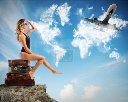 Photo pour Touriste femme assis sur des valises et regarde les avions - image libre de droit