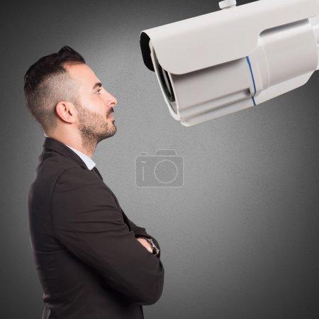 Photo pour Confiant, homme d'affaires se penche sur une caméra de surveillance grand - image libre de droit