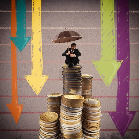 businessman with umbrella sitting on coins