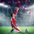 Soccer player exulting on a stadium field...