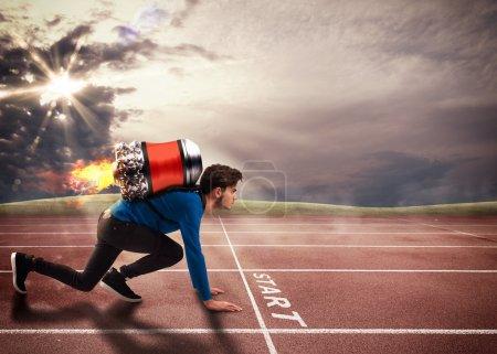 Photo pour Garçon avec fusée sur le dos sur la piste de course - image libre de droit