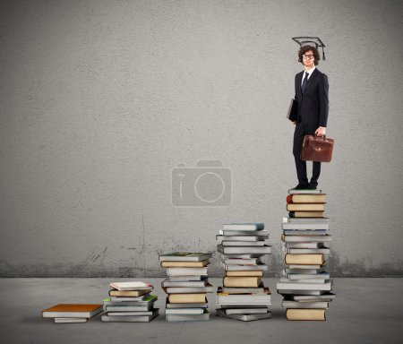 Photo for Man with graduation hat standing on scale with books - Royalty Free Image