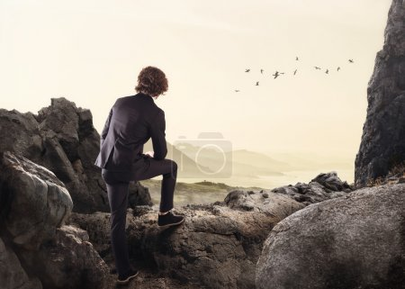 Businessman leaning on a rock