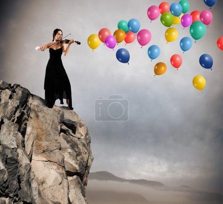 Photo pour Violoniste joue sur une montagne avec des ballons colorés volants - image libre de droit
