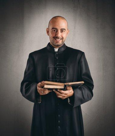 Photo pour Portrait d'un prêtre heureux qui lit une bible - image libre de droit