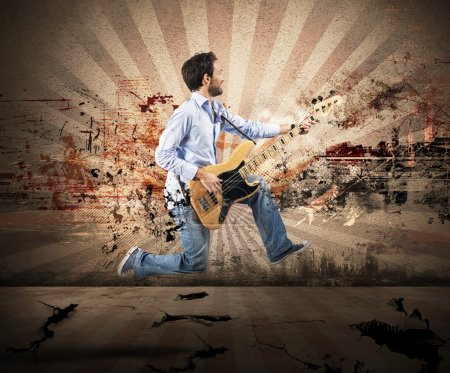 Photo for Man jumping with bass guitar during a performance - Royalty Free Image