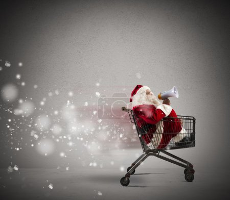 Photo for Fast Santa Claus in a shopping cart announcement through megaphone - Royalty Free Image