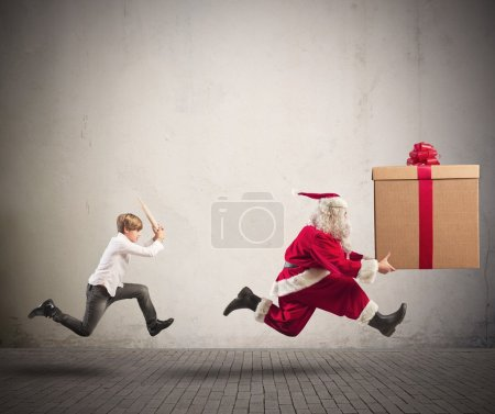 Photo for Running angry child chasing Santa Claus with a big present - Royalty Free Image