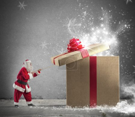 Photo for Santa Claus opening a big red gift - Royalty Free Image