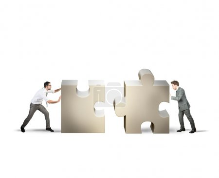 Two businessman pushing puzzle pieces