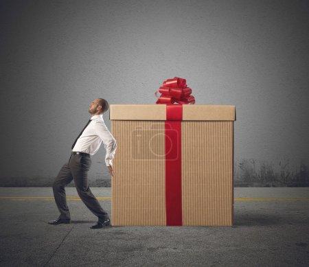 Photo pour Un homme d'affaires fatigué pousse lourd grand cadeau - image libre de droit