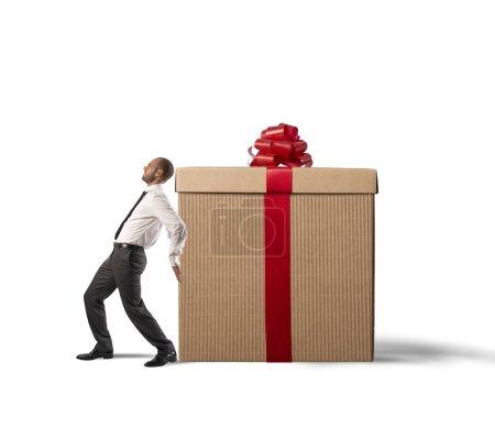 Photo pour Un homme d'affaires fatigué pousse boîte cadeau lourd - image libre de droit