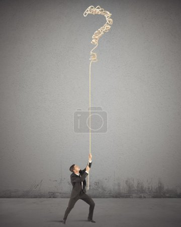 Photo for Businessman trying to solve the complicated tangle - Royalty Free Image