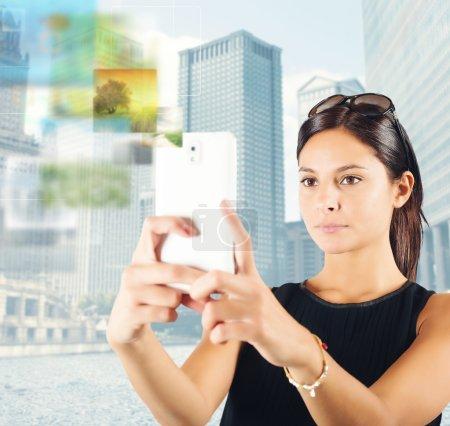 Photo pour Woman photographs the city with her mobile phone - image libre de droit