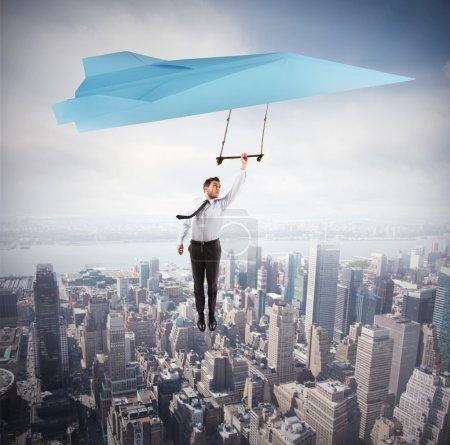 Businessman flying above urban landscape
