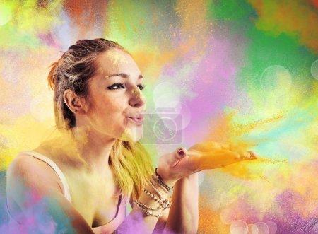 Photo pour Fille soufflant la poussière colorée comme un arc-en-ciel - image libre de droit