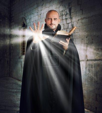 Photo pour Le prêtre avec la Bible émet de la lumière - image libre de droit