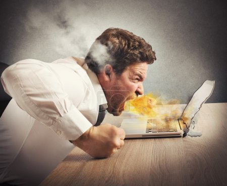 Photo for Businessman spits fire and melts the computer - Royalty Free Image