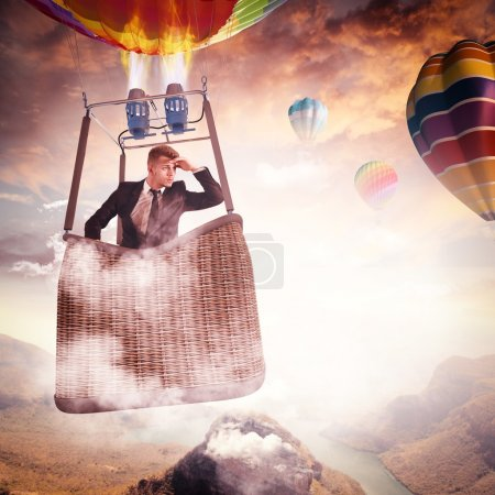Photo for Businessman looking for new perspectives in a hot air balloon - Royalty Free Image