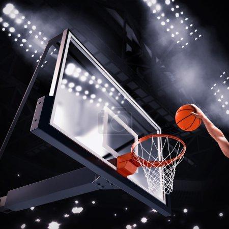 Photo pour Joueur lance le ballon dans le panier au cours du match de basket - image libre de droit