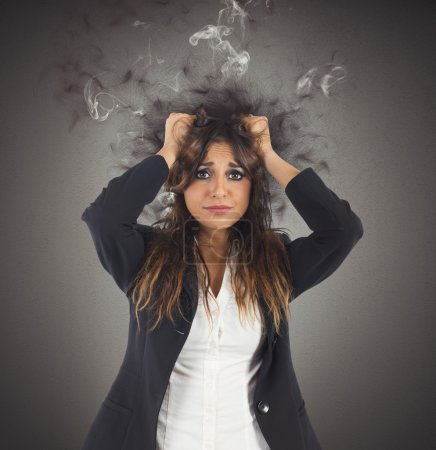 Photo for Stressed and desperate businesswoman with her head in smoke - Royalty Free Image