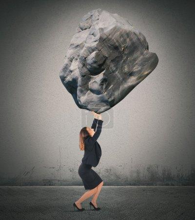 Photo pour Femme d'affaires tenant un gros rocher lourd - image libre de droit