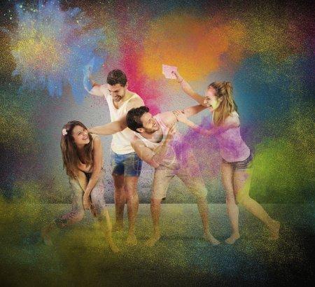 Photo pour Amis jouent et s'amusent avec des poudres colorées - image libre de droit