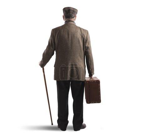 Photo pour Vue arrière du vieil homme avec valise et bâton - image libre de droit