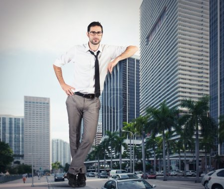 businessman leaning against a skyscraper