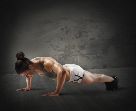 Muscular woman doing push up
