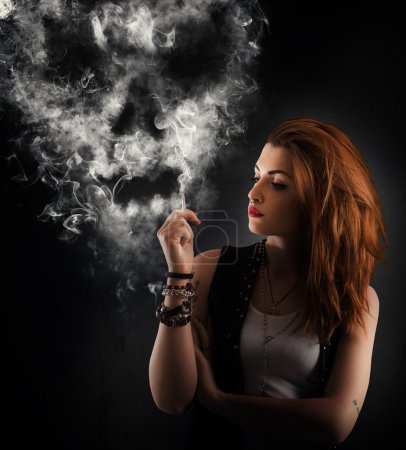 Photo for Girl smokes a cigarette forming a skull - Royalty Free Image