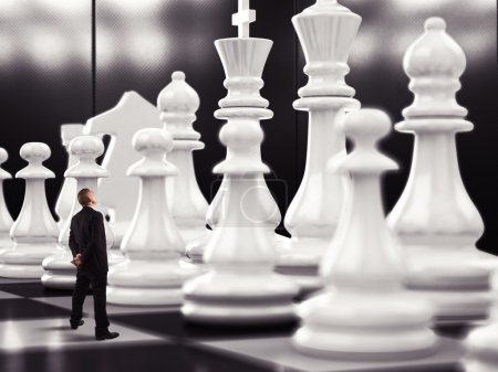 Businessman looks up to chess pawn