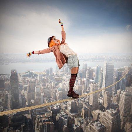 Photo pour Femme clown sur une corde au-dessus de la ville - image libre de droit